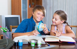 Boy and sister studying with books Stock Photos