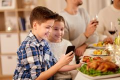 Boy with sister using smartphone at family dinner royalty free stock photography