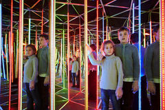Boy and sister wander in semidarkness of mirror labyrinth Stock Photo