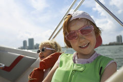 Boy With Sister On Yacht Against Sky Stock Image