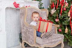 Boy sit in a chair with gifts Stock Photography