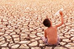 Boy sit on dry ground Stock Image