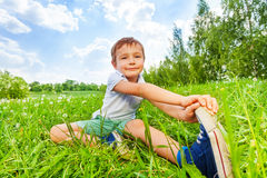 Boy sit on a grass and does gymnastics Royalty Free Stock Images