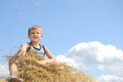 Boy sit on a hayrick and throw a straw Royalty Free Stock Images