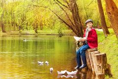 Boy sit near pond playing with white paper boats Royalty Free Stock Images