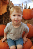 Boy_sit_pumpkin Stockfoto