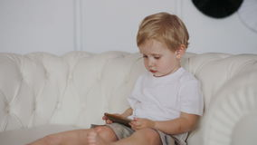 Boy sit on the sofa and watch cartoon. On the smartphone stock video footage