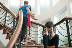The boy sit on the stairs at home, parents quarrel. Family probl. Ems concept Stock Images