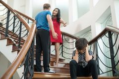 The boy sit on the stairs at home, parents quarrel. Family probl. Ems concept Royalty Free Stock Photography