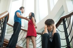 The boy sit on the stairs at home, parents quarrel. Family problems concept royalty free stock images