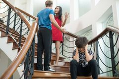 The boy sit on the stairs at home, parents quarrel. Family probl. Ems concept Stock Photos
