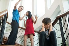 The boy sit on the stairs at home, parents quarrel. Family probl. Ems concept Stock Photo