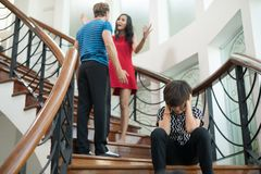 The boy sit on the stairs at home, parents quarrel. Family probl. Ems concept Royalty Free Stock Photo