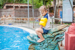 A boy sits on the Asian statue Royalty Free Stock Photo