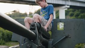 The boy sits astride an artillery gun. Museum exhibit of military equipment. Children`s education stock video footage