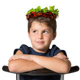 Boy sits astride a chair. Very beautiful seven year old boy in carnival wearing a crown of shiny green and red leaf Stock Photo