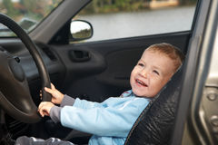The boy sits in the automobile Stock Photography