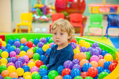 Boy sits in the balls in the game room. Todler boy sits in the balls in the game room Stock Photography