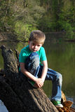The boy sits on the banks of the river in the forest. Sad boy six years sitting on the bank of the river in the forest Royalty Free Stock Photography