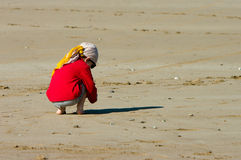 A boy sits on the beach Royalty Free Stock Photos