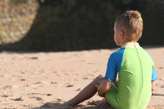 Boy sits on beach. A 6 year old boy sits alone on a beach watching the waves crash over a wall Stock Photo