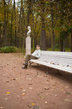 The boy sits on bench in autumn park Royalty Free Stock Photo