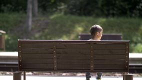 Boy sits on a bench at the railway station and waits for the train back view outdoors royalty free stock photography