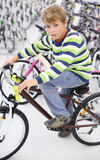 Boy sits on bicycle and looks at camera Stock Image