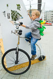 A boy sits on a bicycle. Boy sitting on a toy wheeled vehicle stock image
