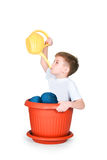 The boy sits in the big flowerpot. On a white background Royalty Free Stock Photo