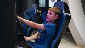 The boy sits in a chair racing car playing a video game. The view from the side. The boy`s face shows emotion. Good mood stock footage