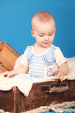 The boy sits in the chest in a sailor suit, and pulls his hand to the rope Stock Photography