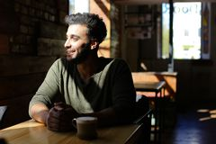 Boyfriend waiting for girt to make proposal in caf . Boy sits in comfortable caf and drinks coffee. Smiling man has dimples, beard, full lips and black hair Royalty Free Stock Photo