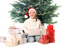 The boy sits with cristmas gifts and notebook Stock Image