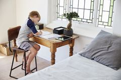 Boy Sits At Desk In Bedroom With Digital Tablet Doing Homework Royalty Free Stock Photos