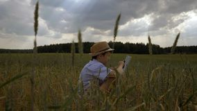 Boy sits in a field against beautiful clouds and uses a tablet in the evening stock photography