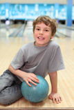Boy sits on floor with ball in bowling club Royalty Free Stock Photos