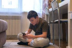 Boy sits on the floor and plays on the smartphone royalty free stock photography