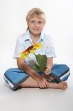 A boy sits on a floor with a sunflower in hands. He is happy. A background is white Royalty Free Stock Photography