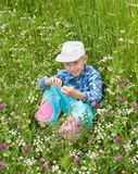 The boy sits in a grass. Among wild flowers stock photography