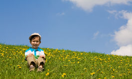 Boy sits on a grass Royalty Free Stock Image