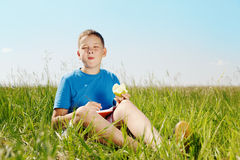 Summer portrait of the boy. The boy sits on a grass and eats a green apple royalty free stock images