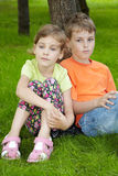 Boy sits on grass, his sister sits next to him. Boy in orange t-shirt sits on grass, leaning his back on trunk of tree and his younger sister sits next to him Stock Image
