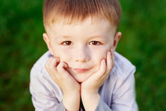 Boy sits on the green grass in the summer park close up Stock Photo