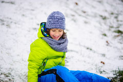 Boy sits on the ground which is slightly covered with the first snow. Royalty Free Stock Image