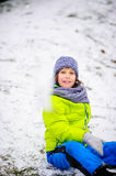 Boy sits on the ground which is slightly covered with the first snow. Royalty Free Stock Photos
