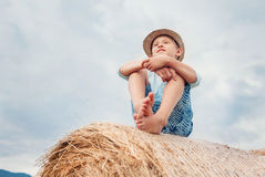 Boy sits on the haystack top with sunny sky background Royalty Free Stock Photo
