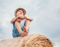 Boy sits on the haystack top with sunny sky background Stock Images