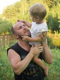 The boy sits on his father`s shoulder royalty free stock photos
