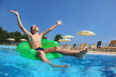 Boy sits on an inflatable arm-chair in pool. Boy sits on an inflatable arm-chair in  pool and with gladness lifts hands and head upwards in sky, underwater Royalty Free Stock Photos